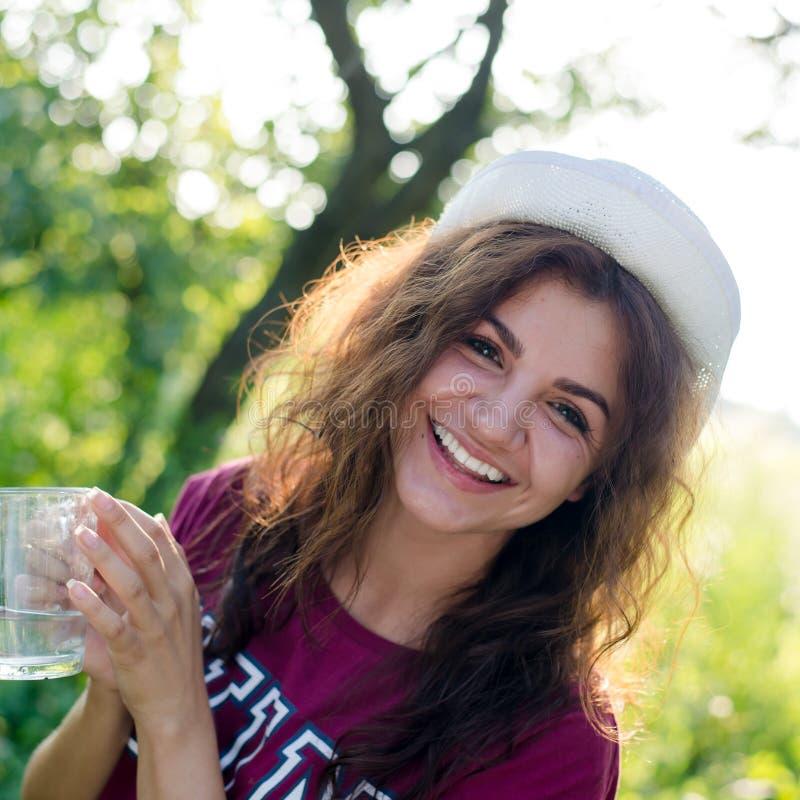 美丽的深色的少妇画象白色行家帽子愉快的微笑的举行的玻璃水的在绿色summe的 免版税库存照片