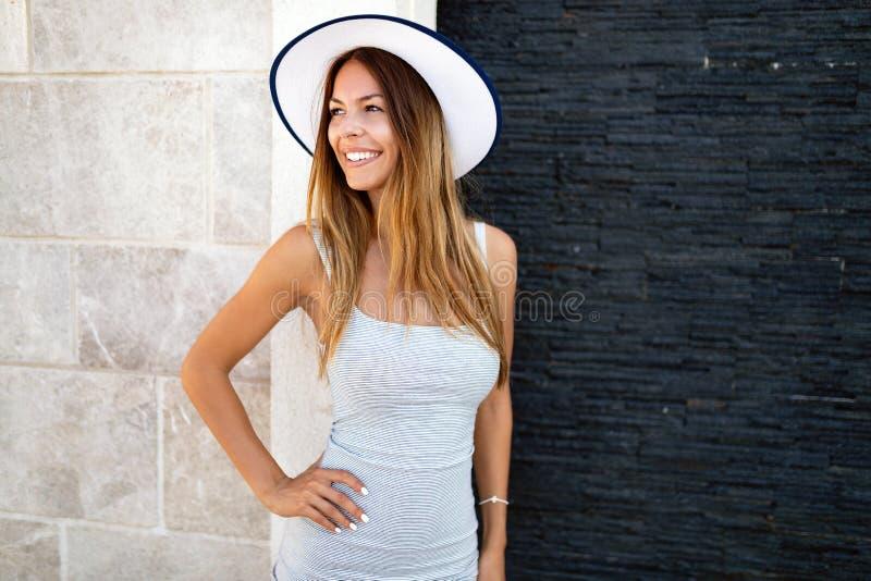 美丽的深色的年轻女人佩带的礼服和帽子,微笑室外 库存照片