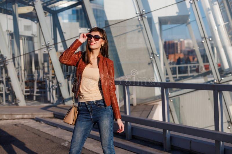 美丽的深色的年轻女人画象精密红褐色的夹克、牛仔布牛仔裤和太阳镜的 真皮袋子,高跟鞋 免版税库存照片