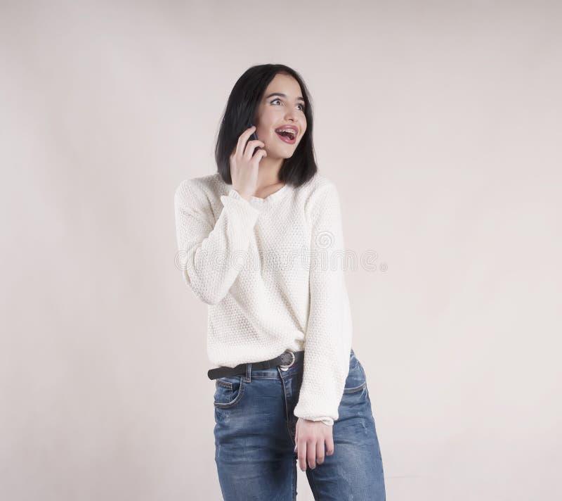 美丽的深色的有电话演播室的女孩佩带的牛仔裤毛线衣 免版税库存图片