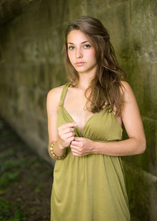 美丽的深色的礼服绿色摆在的年轻人 图库摄影