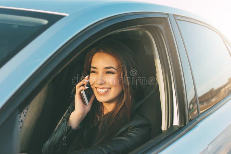 美丽的深色的长发年轻亚裔妇女驾驶和讲话由手机 免版税库存照片