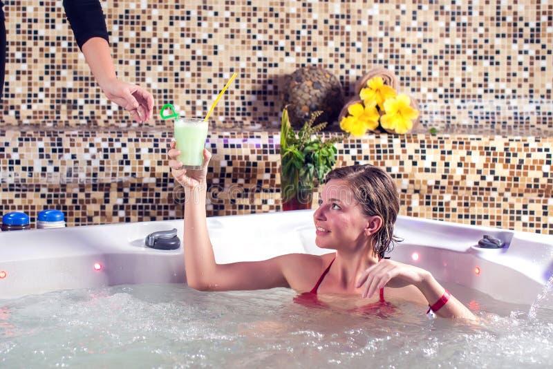 美丽的温泉 享用极可意浴缸和新鲜的汁液在温泉中心的年轻女人 免版税库存照片