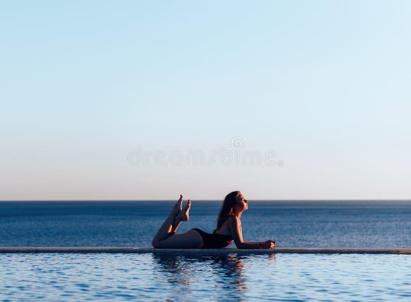 美丽的游泳衣的女孩在拿着太阳镜的海的日落 免版税库存照片