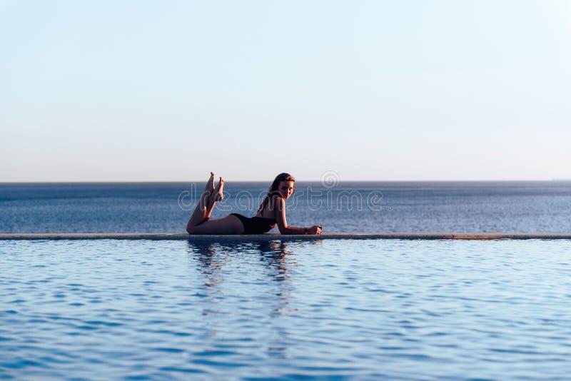 美丽的游泳衣的女孩在拿着太阳镜的海的日落 免版税库存图片