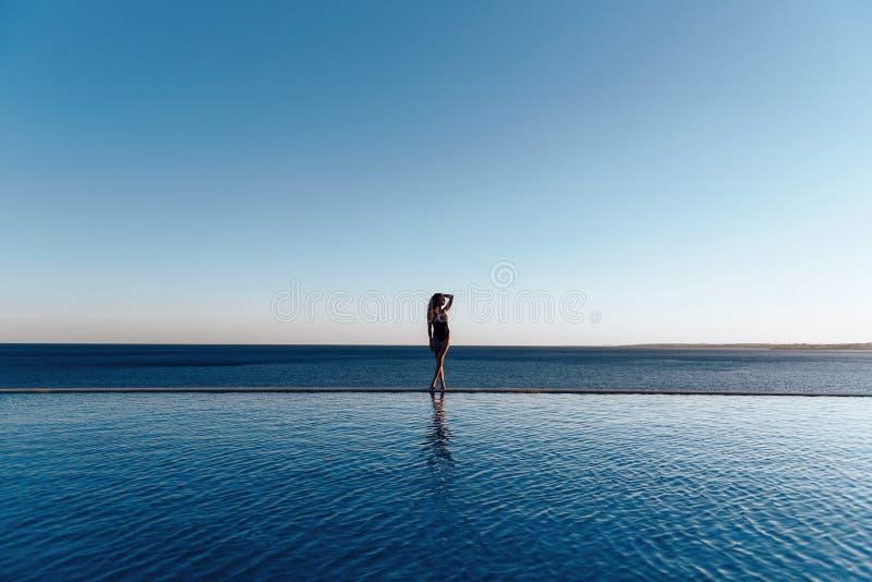 美丽的游泳衣的女孩在拿着太阳镜的海的日落 库存照片