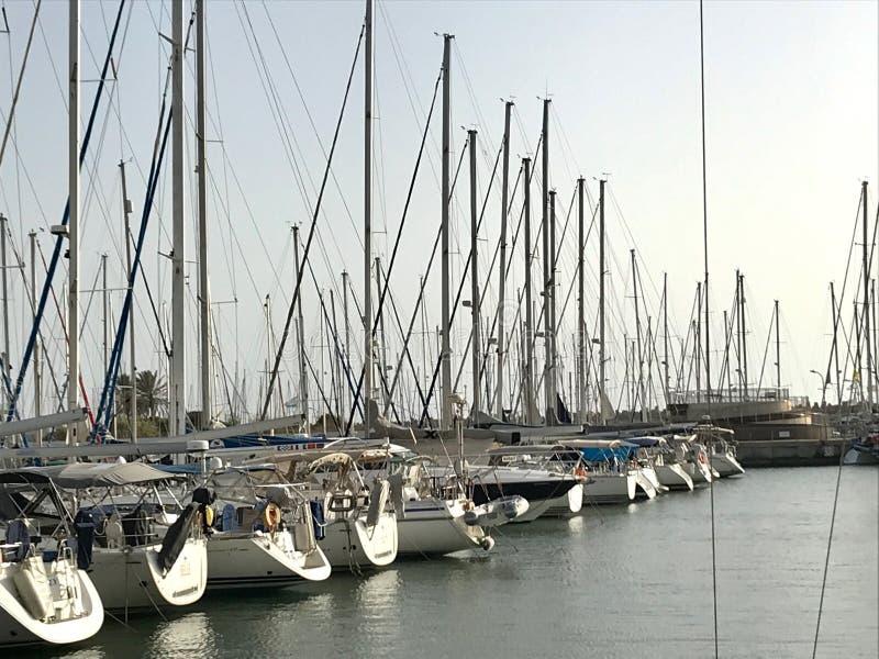 美丽的游艇船被停泊在与其他小船的口岸在蓝色盐味的海 免版税图库摄影