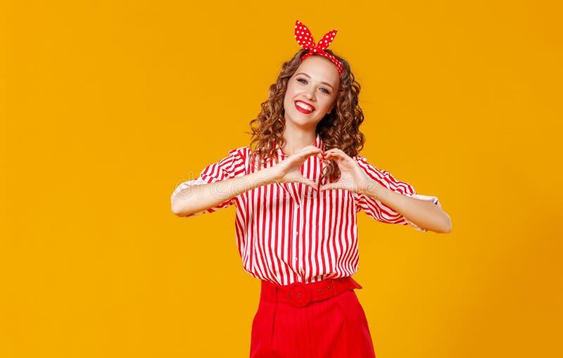 美丽的滑稽的女孩握在心脏的形状的手在黄色背景的 图库摄影