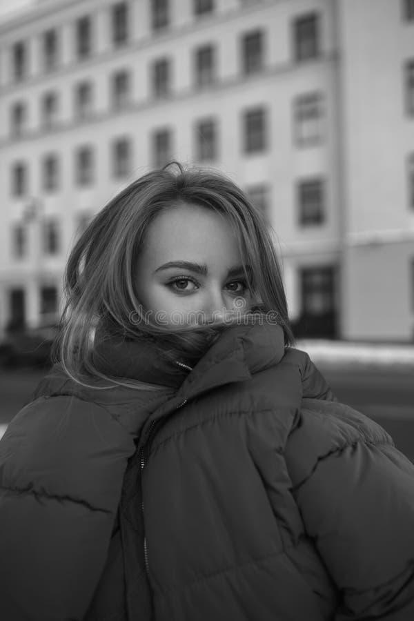 美丽的滑稽的女孩黑白照片巨大的夹克的 库存图片