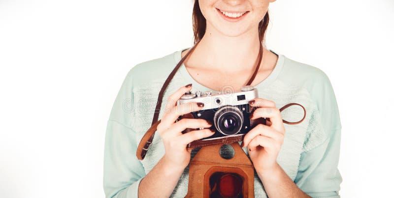美丽的滑稽的有雀斑的少年女孩,17-18岁,与减速火箭的照相机在她的手上,隔绝在白色背景 免版税库存照片