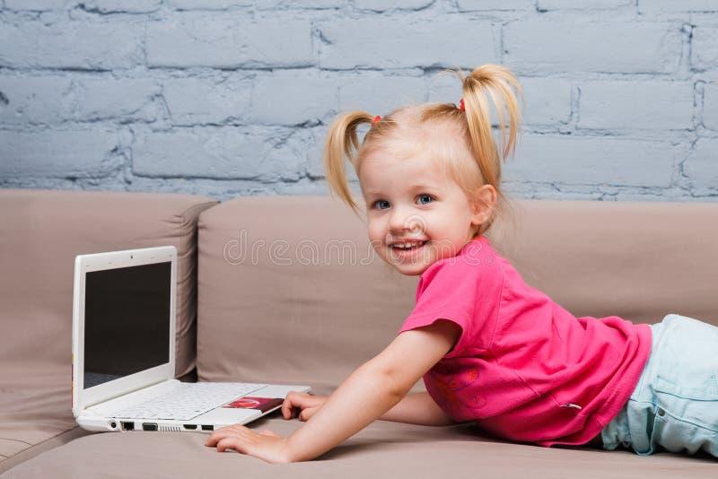 美丽的滑稽的白肤金发的女孩两年的孩子在长沙发说谎户内并且使用与co的白色便携式计算机技术 免版税图库摄影