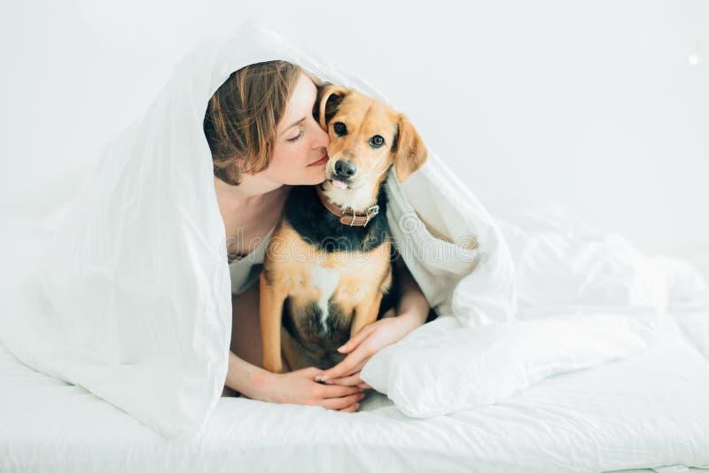 美丽的激动的年轻女人和她逗人喜爱的杂种狗狗是无所事事,看照相机,当用一条毯子报道的说谎在床上时 免版税库存图片