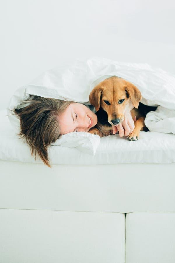 美丽的激动的年轻女人和她逗人喜爱的杂种狗狗是无所事事,看照相机,当用一条毯子报道的说谎在床上时 免版税库存照片