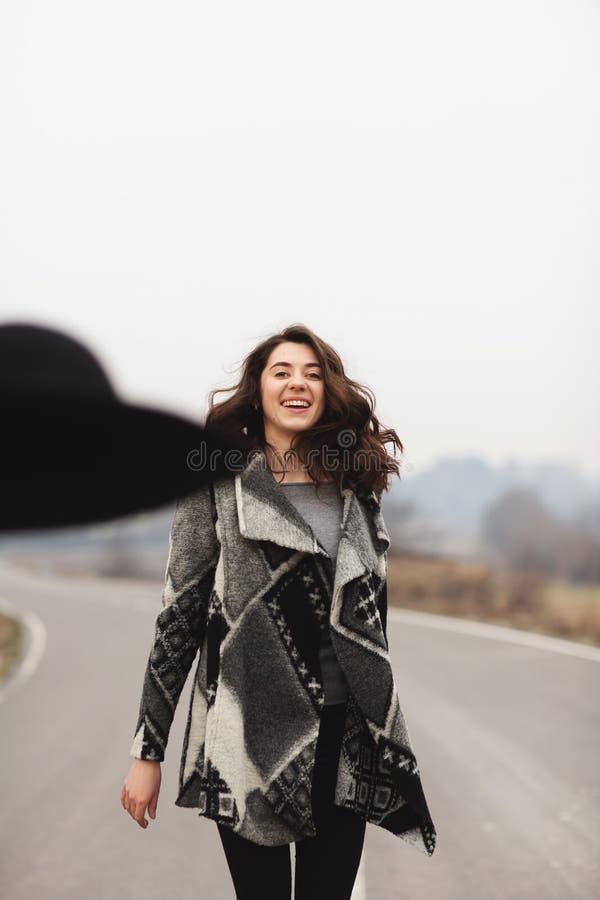 美丽的灰色羊毛衫和黑帽会议乘驾的愉快的妇女  图库摄影
