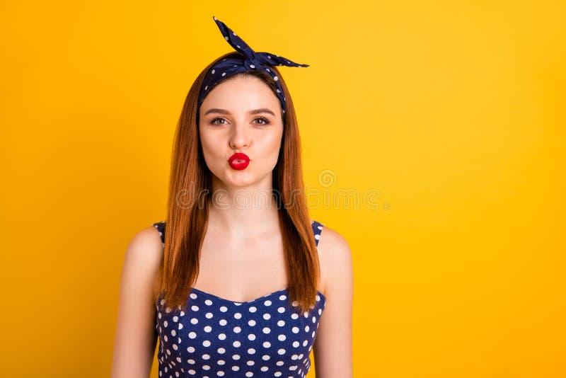 美丽的狡猾的夫人红色口红照片送空气亲吻穿戴偶然被加点的坦克头等的头饰带被隔绝的生动的黄色 库存照片