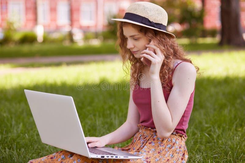 美丽的狡猾的头发的妇女照片坐与膝上型计算机和电话的绿草在手上,谈话在电话,有重要 免版税库存图片
