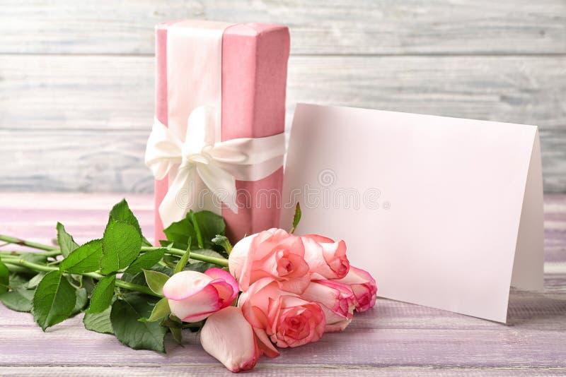 美丽的玫瑰、礼物盒和贺卡在木桌上 免版税库存图片