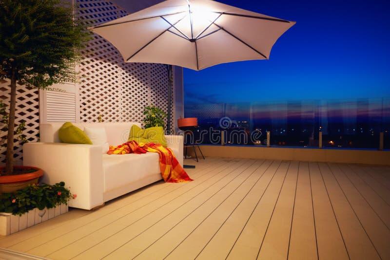 美丽的现代屋顶露台,大阳台有晚上城市视图 免版税库存照片