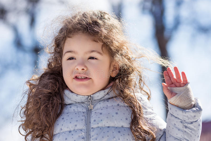 美丽的甜卷曲白肤金发的女孩室外使用在公园4岁 免版税库存图片