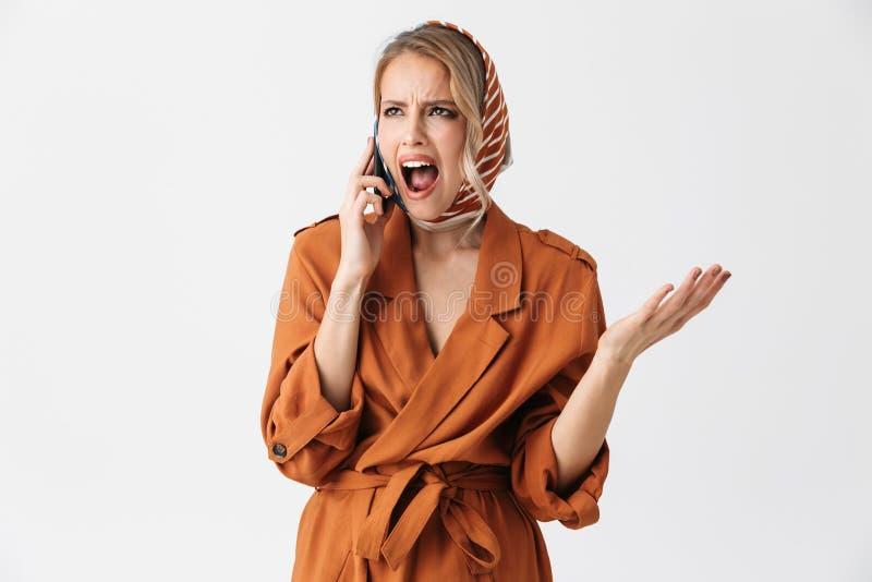 美丽的生气的年轻女人佩带的丝绸围巾被隔绝在谈话白色的背景由手机 免版税图库摄影