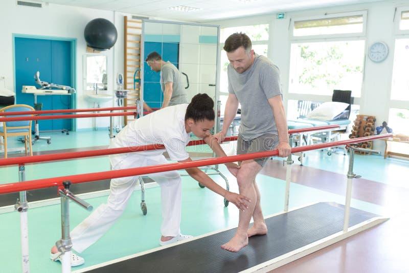 美丽的生理治疗师帮助的患者在踏车解决 库存照片
