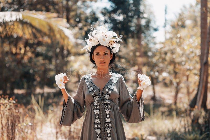 美丽的用赤素馨花花做的赤素馨花花和年轻女人佩带的花圈在手上户外 库存照片