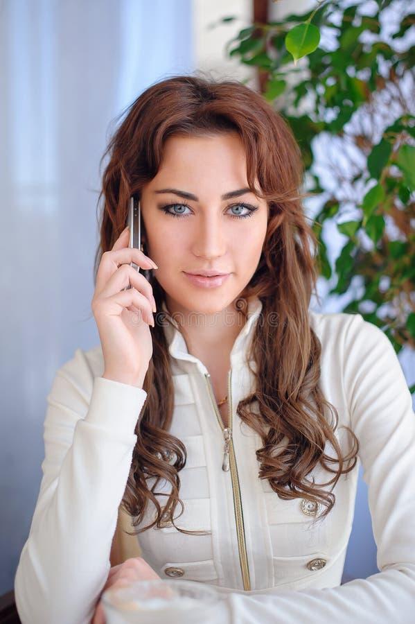 美丽的电池女孩电话联系的妇女年轻人 免版税库存图片