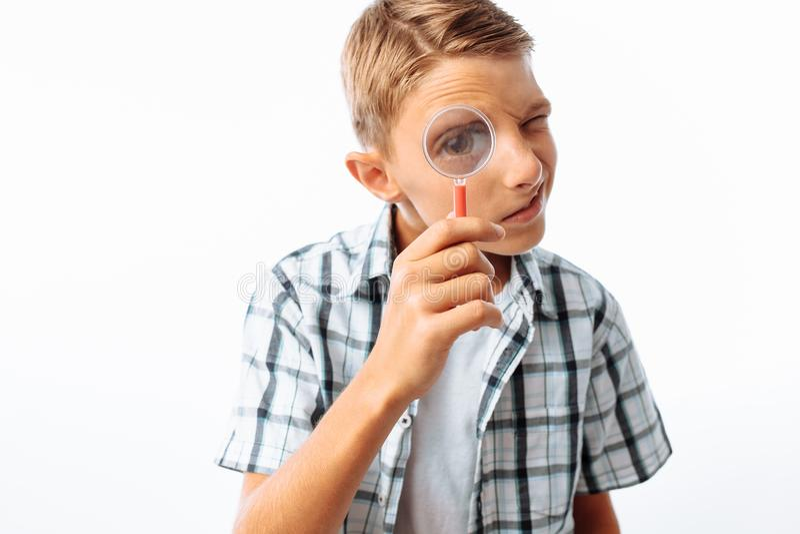 美丽的男孩看通过放大镜的,一个少年寻找,在演播室,特写镜头 库存照片