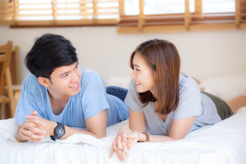 美丽的画象年轻亚洲夫妇在卧室一起放松并且在家满意了,说谎在床上的家庭 免版税库存图片