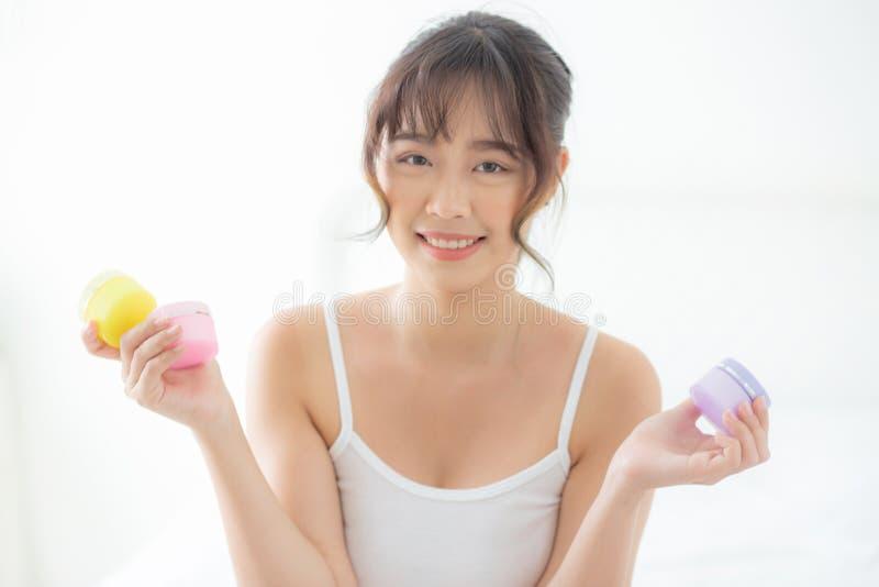 美丽的画象年轻亚裔妇女有吸引力的举行的瓶子面孔的奶油和化妆水皮肤新鲜和软在屋子 库存图片