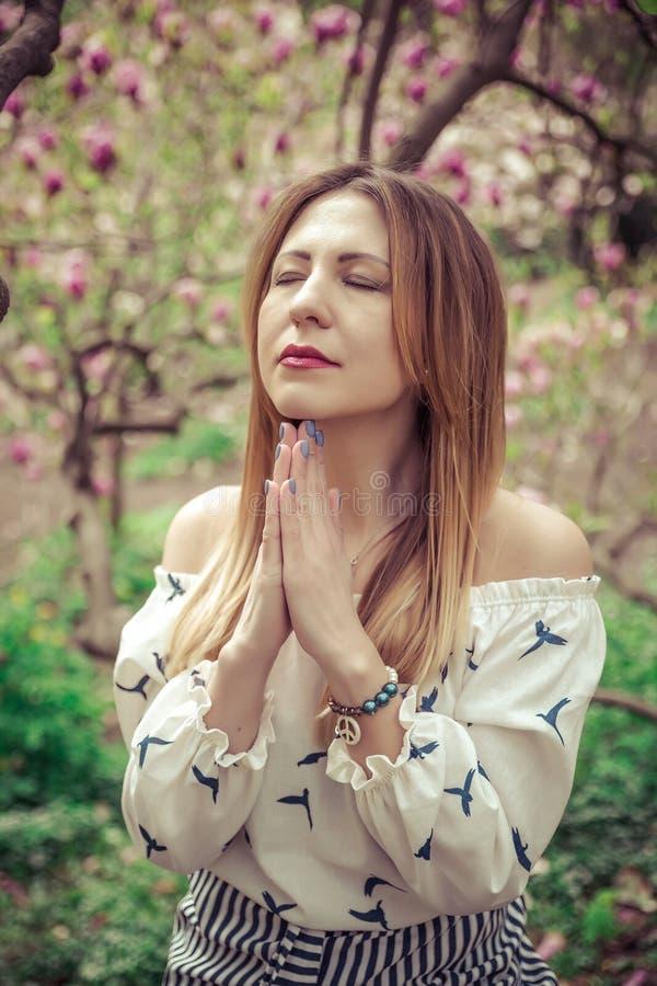 年轻美丽的白种人妇女在木兰开花的春天庭院里  女孩在庭院里在一多云天 免版税库存照片
