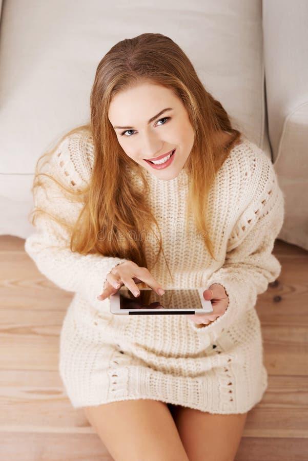 美丽的白种人妇女坐与片剂的地板。 免版税库存图片