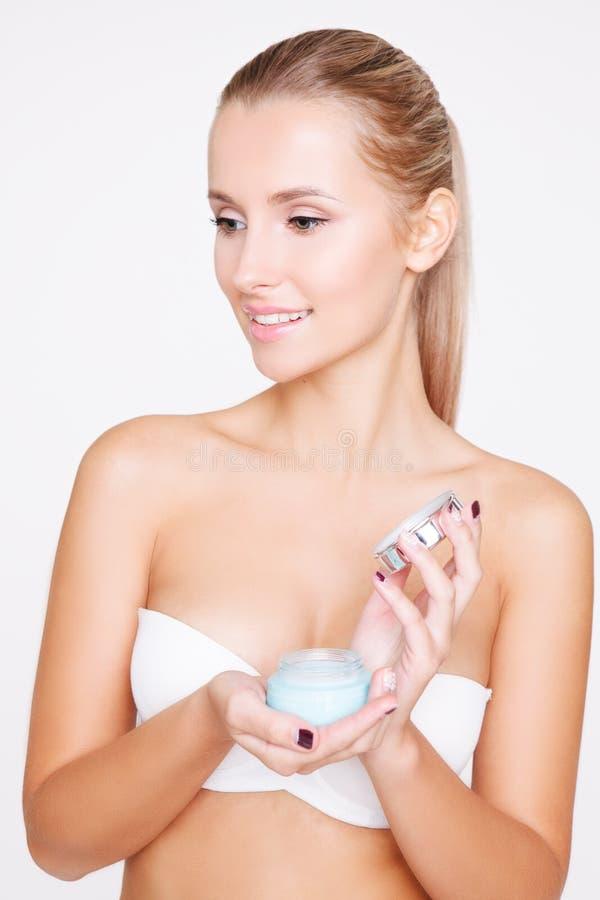 年轻美丽的白种人妇女开头奶油画象被隔绝在灰色背景 清洁面孔,完善的皮肤 库存图片