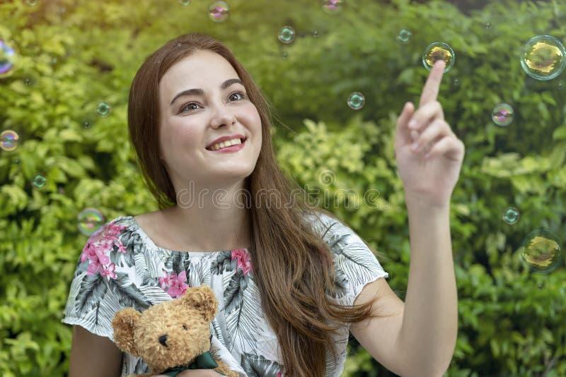美丽的白种人妇女拥抱玩具熊和演奏肥皂泡室外在公园 放松和自由时间 免版税图库摄影