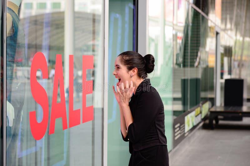 美丽的白种人妇女激动,当在商店看见在销售衣物时尚中的价牌 免版税库存照片