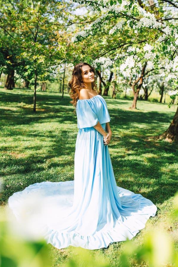 美丽的白种人妇女画象长的礼服的在春天开花的庭院,长的头发和组成,时尚照片 库存图片
