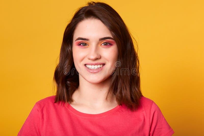 美丽的白种人年轻女人接近的画象有桃红色和橙色魅力的组成,并且暴牙的微笑,模型有愉快的脸面护理 图库摄影