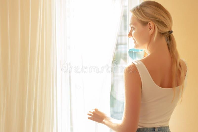美丽的白种人年轻女人饮用的咖啡在房子,咖啡因的早晨做刷新的有吸引力的美女神色 图库摄影