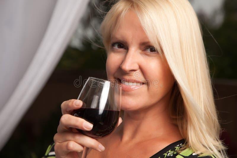 美丽的白肤金发的享用的酒 库存图片