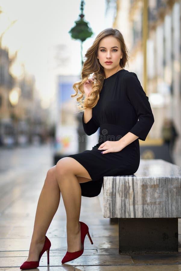 美丽的白肤金发的俄国妇女在都市背景中 免版税库存照片