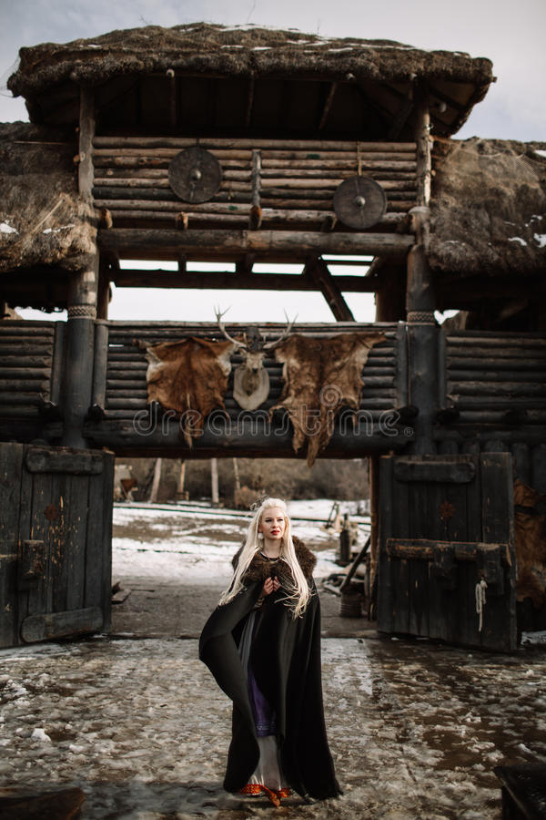 美丽的白肤金发的北欧海盗在一个黑斗篷穿戴了 免版税库存图片