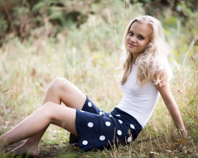 美丽的白肤金发的十几岁的女孩外面在森林 图库摄影