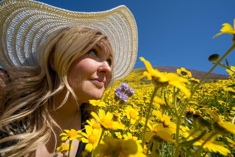 美丽的白肤金发的在一个黄色野花领域的妇女佩带的白色草帽,看一天空蔚蓝在春天 采取在卡里索 免版税库存照片