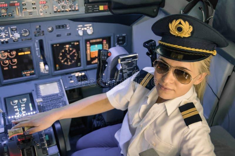 美丽的白肤金发的在飞行防真器的妇女试验佩带的制服 免版税图库摄影