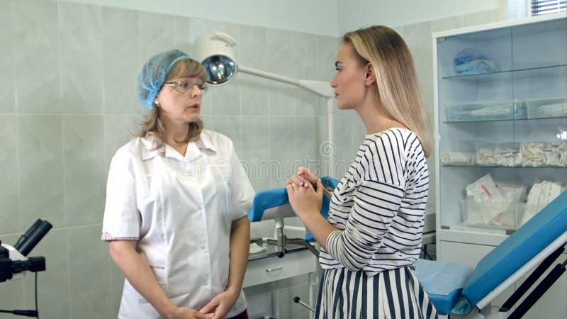 美丽的白肤金发的女孩与妇产科医师协商 免版税库存图片