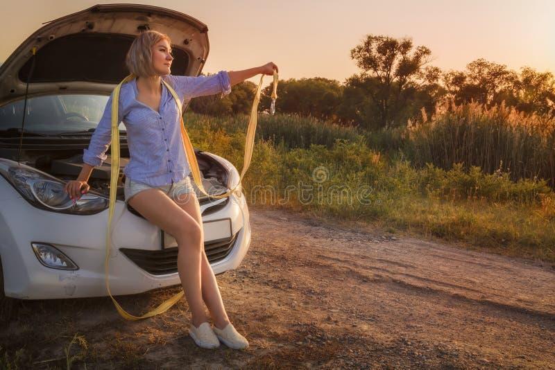 美丽的白肤金发的女孩与船缆在一辆残破的汽车的敞篷坐在日落的光芒的一条农村路 免版税库存图片