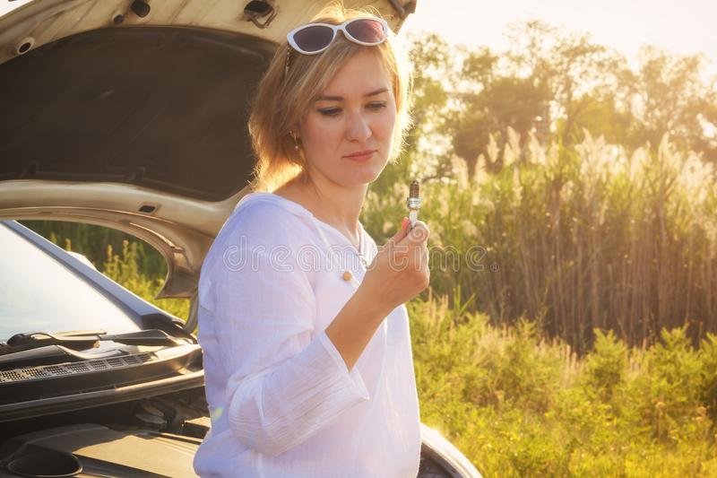 美丽的白肤金发的女孩参与修理在乡下公路的一辆汽车并且拿着板钳,并且火花塞光芒 图库摄影