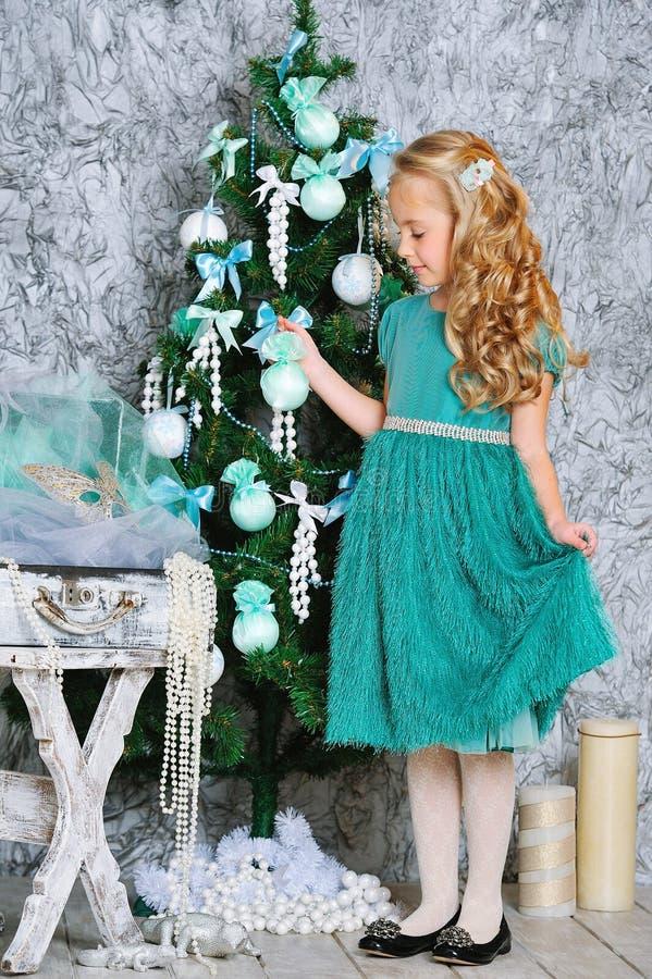 美丽的白肤金发的女孩和圣诞树 库存图片