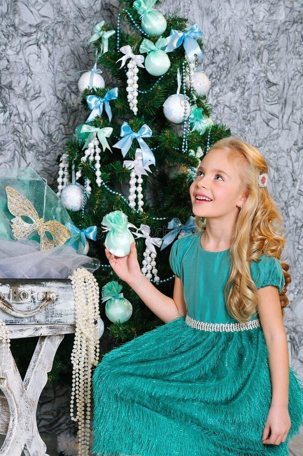 美丽的白肤金发的女孩和圣诞树 免版税库存照片
