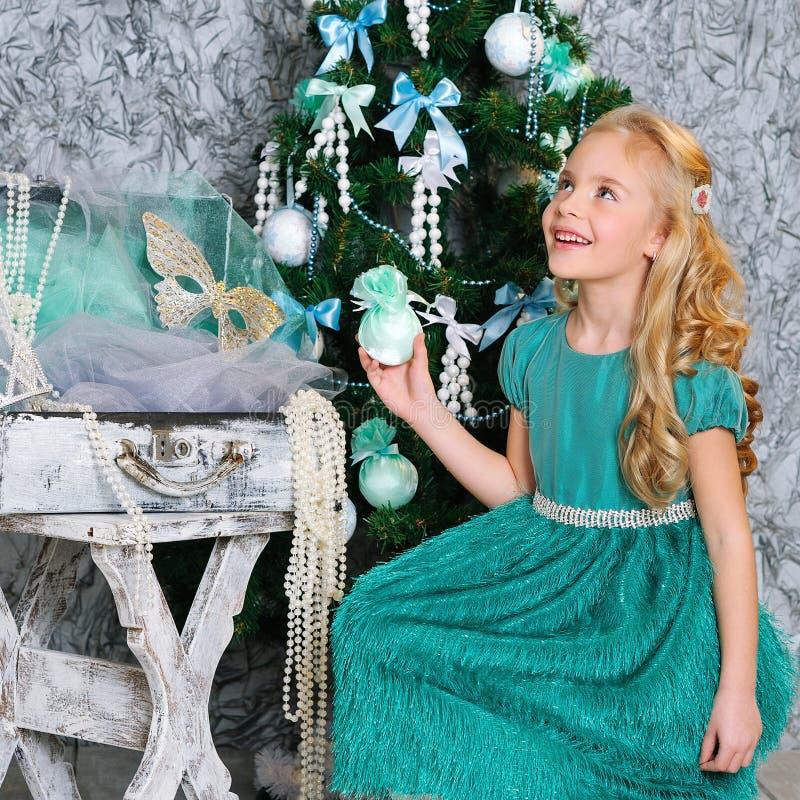美丽的白肤金发的女孩和圣诞树 免版税库存图片